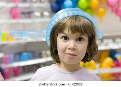 little smiling funny girl  puts  colander on her head