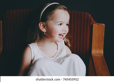 A little smiling girl 3 years old is sitting in a retro chair on a dark background.