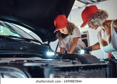 Little smiling girl is curious about car's engine at auto service with her mother, which is doing man's job.