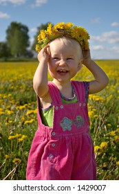 little smiling girl with dandelion wreath