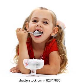 Little smiling girl eating ice cream