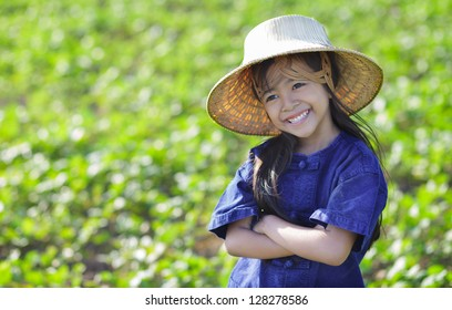 Little smiling girl farmer on green fields, Outdoor portrait