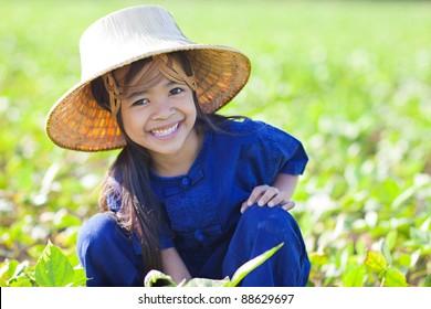 Little smiling girl farmer on green fields, Outdoor portrait