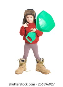 Little smiling girl in father's boots and ear flap hat, isolated on white