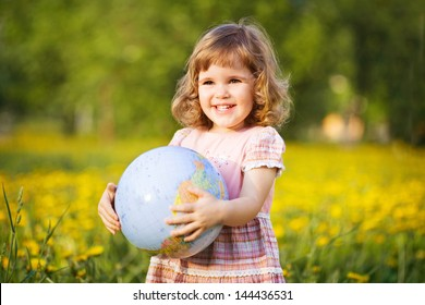 Little smiling girl with a globe in a summer field