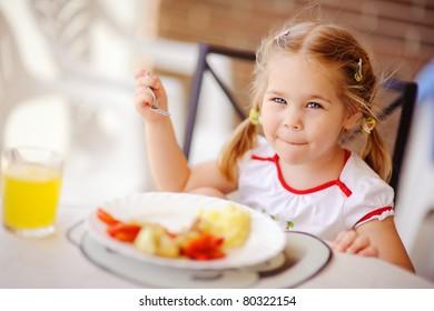 little smiling girl have a breakfast in outdoor cafe