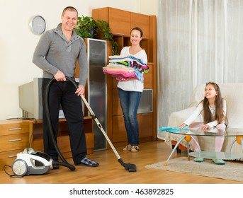 Little smiling girl helping happy parents to clean at living room. Focus on man