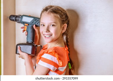 Little smiling girl holding a drill.