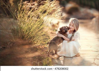 little smiling girl with long blond hair in white dress sitting on the road in the park with small dog