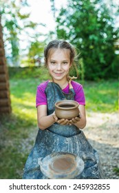 Little smiling girl produced on potters wheel pot.