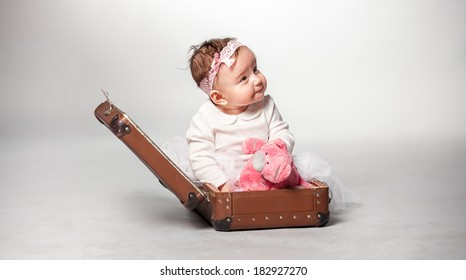 Little smiling girl sitting in suitcase with pink teddy bear
