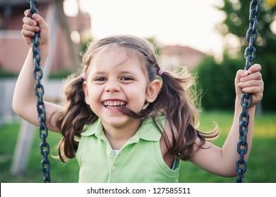 Little smiling girl swinging close up portrait.