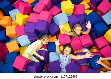 Little smiling girls and joyfully playing with colorful soft cubes in the playroom