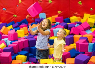 Little smiling girls playing with colourful sotf cubes in the amusement park