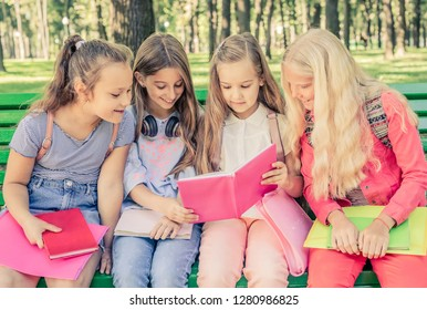 Little smiling girls reading pink book together on a bench