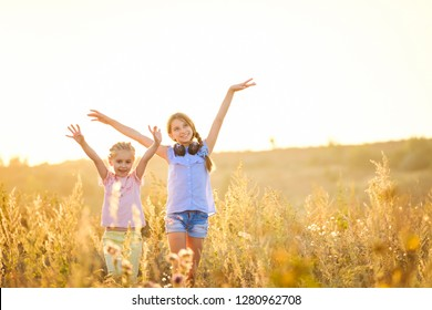 Little smiling girls stand on sunshine evening field with joyfully raised hands