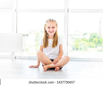 Little smiling kid girl sitting on the floor in white room with bare foot
