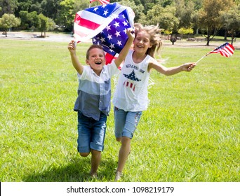 Little smiling patriotic girl  with long blond hair and boy holding an american flag waving in the wind outdoors on beautiful summer day. National 4 july. Memorial day, Flag day