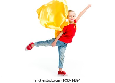 Little smiling supergirl in yellow cape standing on one leg and gesturing by hand isolated on white