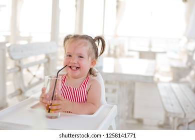 A little smiling toddler girl with two tails and in a striped suit is sitting at a table in a summer cafe in the seaside resort.