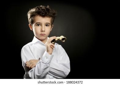 Little snobbish boy with theater binoculars in low key