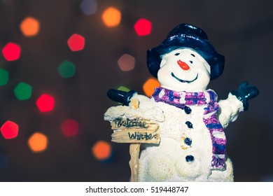 Little Snowman Figurine Welcomes Winter In The Spotlight Christmas Tree Lights Bokeh Background Vintage