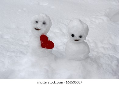 Little snowman offering a red heart to its lover girl
