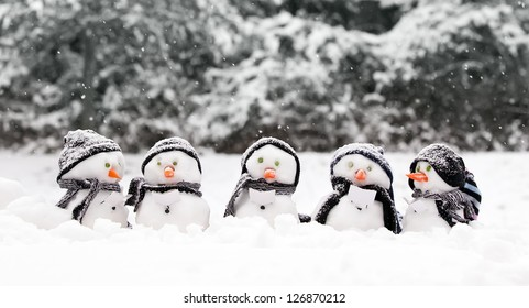 Little snowmen in a group carol singing in the snow