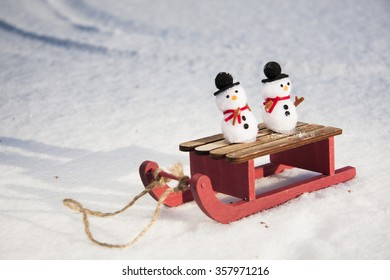 Little snowmen riding on a sledge