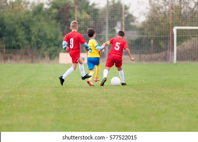 Little soccer player in the battle for the ball against two rival players
