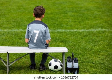 Little soccer player sitting on a wooden bench and watching soccer game. Young substitute player waiting on a soccer bench.