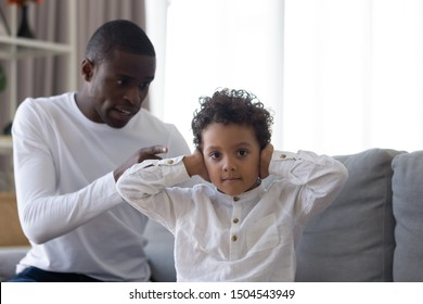 Little son covering ears, ignoring strict angry African American father, looking at camera, annoyed unhappy dad scolding, quarreling, shouting at preschool boy, family generations conflict