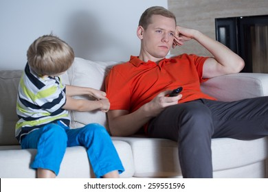 Little son encouraging his tired father for fun