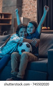Little son and his beautiful mother hugging and cheering while watching a soccer game on couch at home