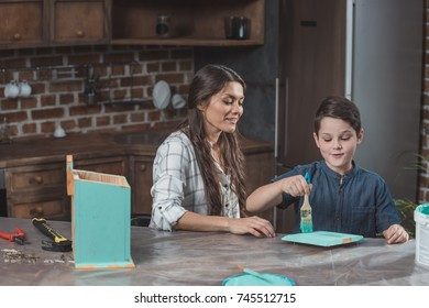 Little son and his beautiful mother sitting at table in kitchen and painting part of wooden birdhouse