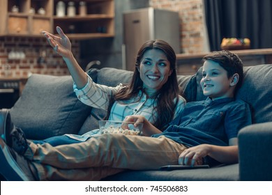 Little son and his young mother talking while watching tv on couch and eating popcorn