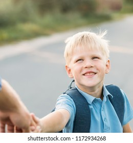 Little son holding father's hand and smiling. Schoolboy with bag smiling, looking at father and smiling. Back to school concept.