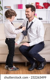 Little son is tying necktie to dad. Father is going to go to work.