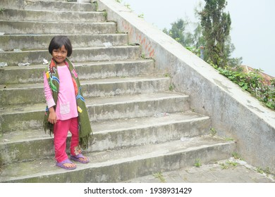 Little Southeast Asian girl smile happily while standing on an outdoor stairway. Indonesian girl wear pink clothes, purple sandals, and Bali fabric