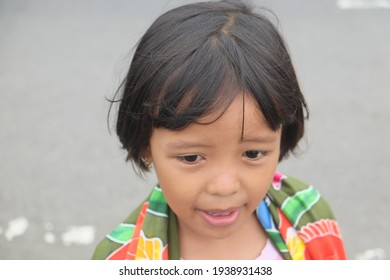 Little Southeast Asian girl smile happily with gray background. Indonesian young girl wear traditional Bali fabric. Javanese lillte girl with grey background