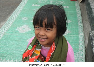 Little Southeast Asian girl smiling wide happily shows off her teeth, looking at the camera. Javanese young girl wear traditional Bali fabric. Little girl with green mat on the background.