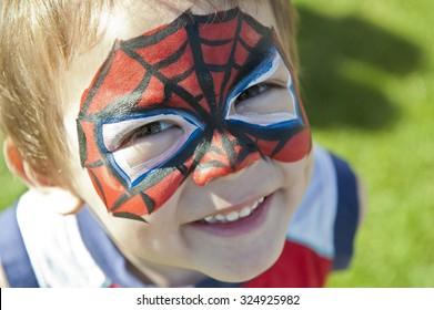 Little spider guy happily wearing face paint