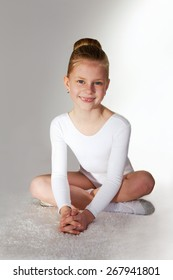 Little sporty girl sitting on the  carpet over grey background.