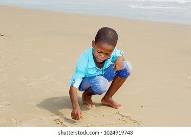 little squatting boy, writing with his fingers in the sand at the beach.