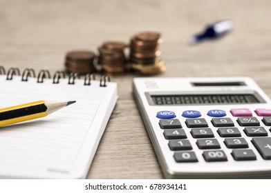 Little stacks of coins with paper block, pencil and calculator