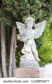 Little stone angel on a tomb or grave  in a churchyard against greenery. Spiritual remembrance or memorial. Close up on the angel