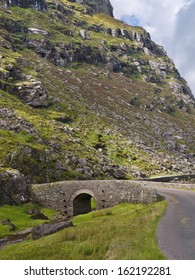 A little stone bridge carries a narrow deserted road across a mountain stream between steep mountain slopes in the rocky terrain near the Gap of Dunloe, famous tourist destination in Kerry, Ireland.