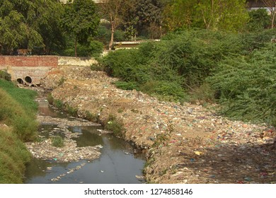 A little stream under the road, culvert. The coast and water is very littered. Environmental pollution in the countries of tropical Asia