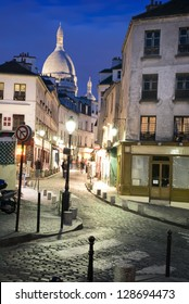 A little street called Rue Norvins at night in Montmartre (Paris, France). Sacre-Coeur in the background.