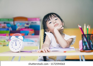 little student asian girl boring study lie down on a table. suffering from headache while doing overwork with learning , homework , study . school children education habit and parent concern concept.